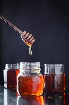 Miele fresco in un barattolo e un mestolo di miele
