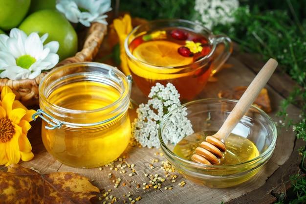 Miele fresco, polline e mele mature su un tavolo di legno