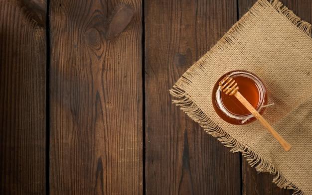 Miele fresco in un barattolo di vetro trasparente e un cucchiaio di legno su un tavolo marrone, vista dall'alto, spazio copia