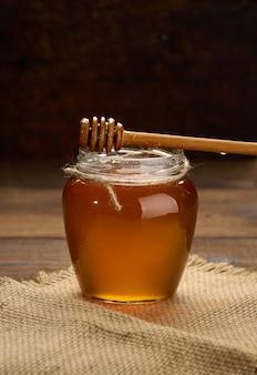 Miele fresco in un barattolo di vetro trasparente e un cucchiaio di legno su un tavolo marrone