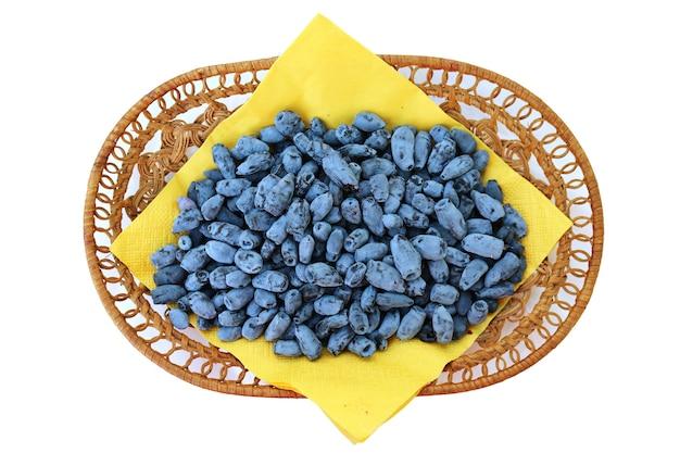 Bacche fresche del caprifoglio su una carta gialla in un piccolo canestro su fondo bianco