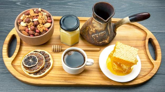 Caffè caldo fresco con tacchino e agrumi secchi, noci e favo su una tavola di legno da cucina. alimento vitaminico utile per il corpo umano