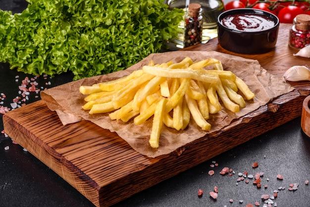 Patatine fritte calde fresche con verdure salate e spezie su uno sfondo di cemento scuro