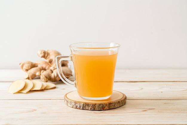 Bicchiere di succo di zenzero fresco e caldo con radici di zenzero - stile di bevanda salutare
