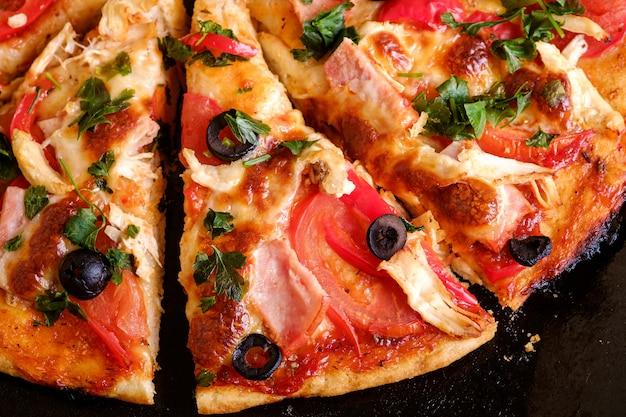 Pizza calda fresca fatta in casa con carne di pollo, prosciutto, pomodoro, mozzarella, olive nere e prezzemolo