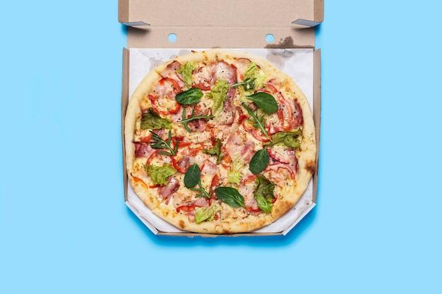 Pizza calda fresca in un pacchetto aperto su un blu