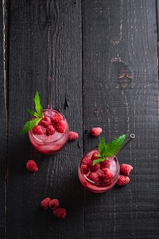 Bevanda di succo di bacche fresche ghiacciate con menta, limonata lampone estivo in due bicchieri con cannucce su fondo di legno scuro, vista dall'alto copia spazio