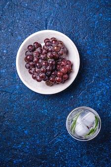 Acqua gassata ghiacciata fresca in vetro con foglia di rosmarino vicino alla ciotola di legno con acini d'uva, sfondo blu con texture, vista dall'alto