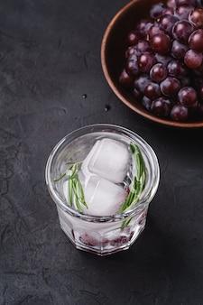 Acqua gassata ghiacciata fresca in vetro con foglia di rosmarino vicino alla ciotola di legno con acini d'uva, superficie di pietra scura, angolo di visione