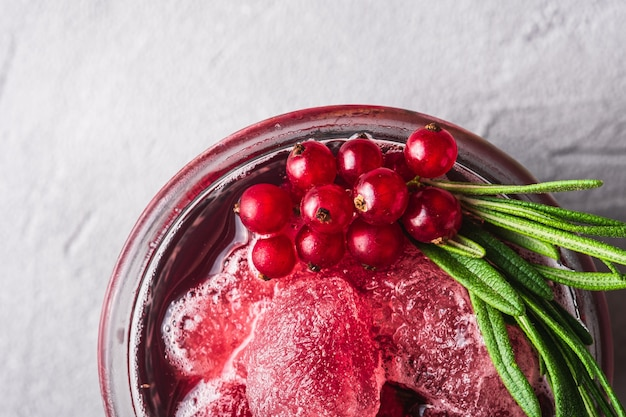 Fresco di ghiaccio freddo cocktail di frutta in vetro, rinfrescante estate ribes rosso berry drink con foglie di rosmarino su pietra sfondo concreto, vista dall'alto macro