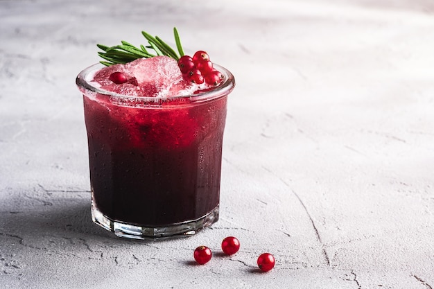 Cocktail di frutta ghiacciata fresca in vetro, rinfrescante bevanda estiva a bacca di ribes rosso con foglia di rosmarino