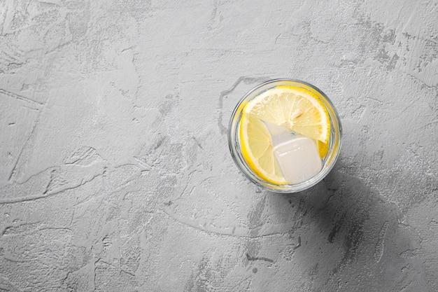 Bevanda di acqua ghiacciata fresca con limone in vetro su sfondo concreto, spazio di copia vista dall'alto