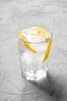 Bere acqua ghiacciata fresca con limone in vetro su cemento