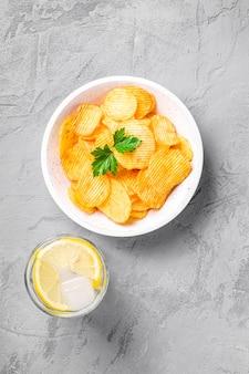 Bevanda fresca di acqua ghiacciata con limone vicino a patatine fritte ondulate dorate fritte con foglia di prezzemolo in ciotola di legno su sfondo di cemento, vista dall'alto