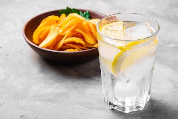 Bere acqua ghiacciata fresca con limone vicino a patatine fritte dorate ondulate