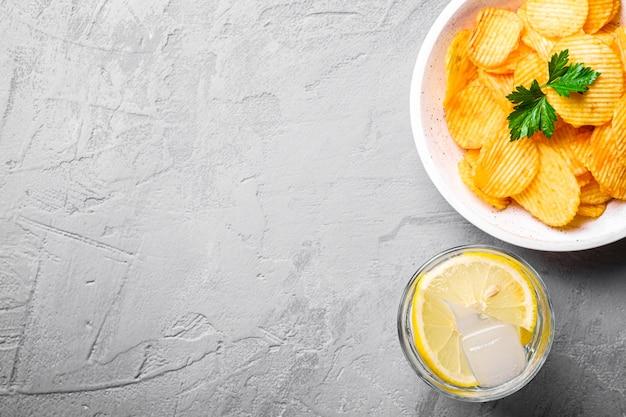 Bere acqua ghiacciata fresca con limone vicino a patatine dorate
