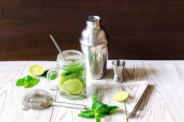 Bevanda estiva fresca e ghiacciata con limonata mojito, set da cocktail con lime a fette, foglie di menta verde brillante, shaker e cucchiaio in tazza trasparente, barattolo di vetro sul tavolo di legno