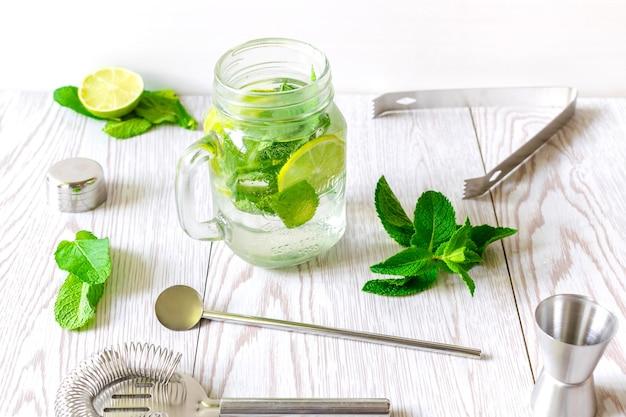 Bevanda estiva fresca e ghiacciata con limonata mojito, cocktail con lime a fette, foglie di menta verde brillante e cubetti di ghiaccio congelati in una tazza trasparente, barattolo di vetro sul tavolo di legno.