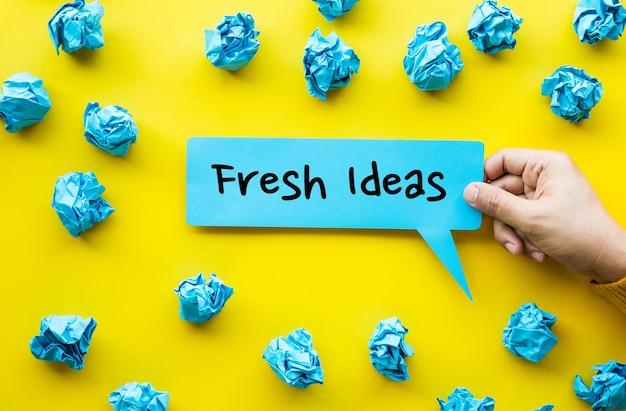 Idea fresca e concetti di creatività con la mano della persona che tiene la carta della bolla e la palla sgualcita della carta