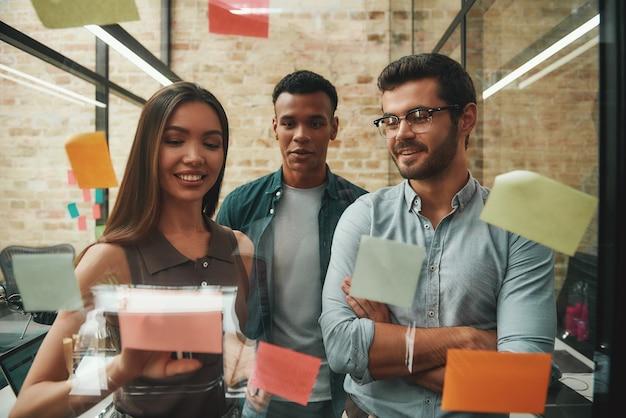 Idee fresche allegri colleghi maschi e femmine che pianificano il processo di lavoro e utilizzano adesivi colorati