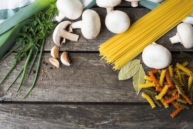 Ingredienti freschi per cucinare pasta, pomodoro e spezie su sfondo tavolo in legno con spazio di copia