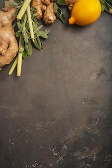 Ingredienti freschi zenzero, citronella, salvia, miele e limone per un tè antiossidante e antinfiammatorio sano su sfondo scuro con spazio di copia. vista dall'alto.