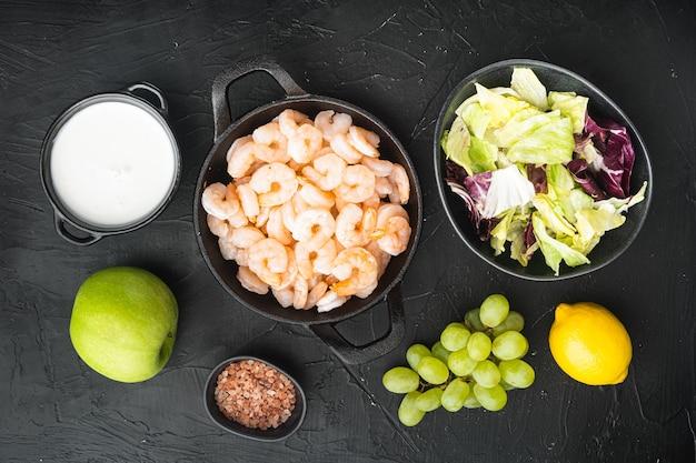 Ingredienti freschi per un gustoso set di insalata di gamberi waldorf, con salsa di mele e uva, su sfondo di pietra nera