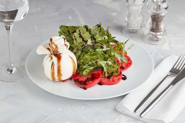 Burrata italiana fresca con fette di pomodoro su un piatto leggero