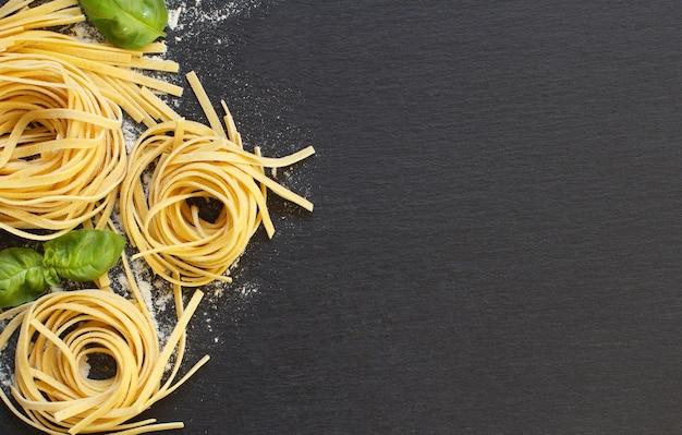 Pasta fresca italiana e basilico su uno sfondo scuro