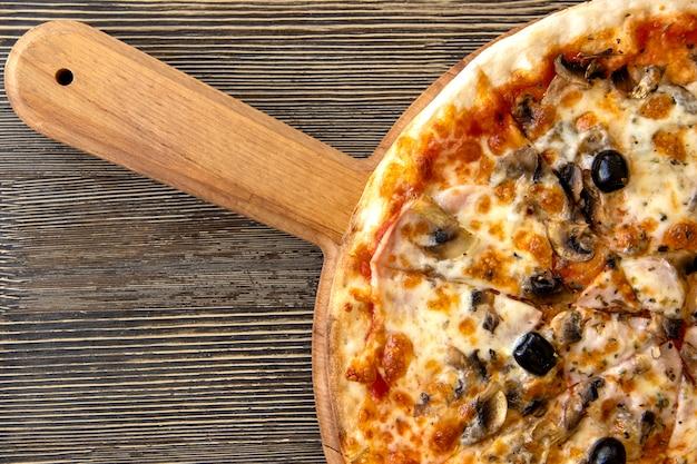 Pizza italiana fresca con funghi, olive e formaggio su un tavolo di legno