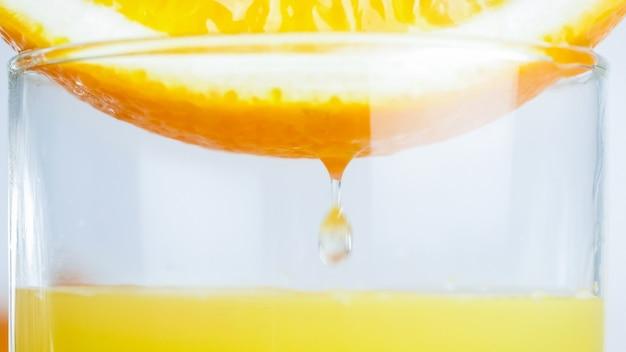 Succo fresco che scorre da metà arancia in vetro.