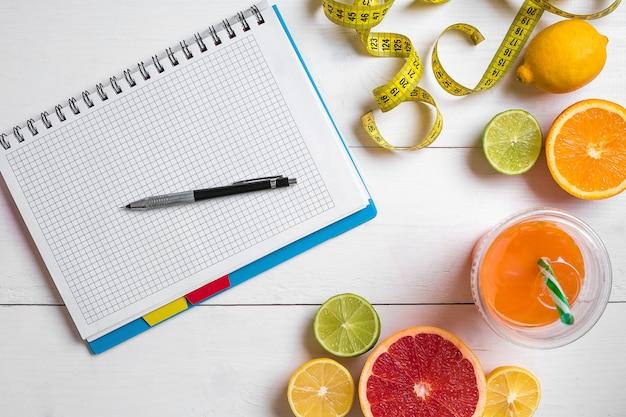 Succo fresco in vetro di agrumi limone pompelmo arancia quaderno con matita su legno bianco...