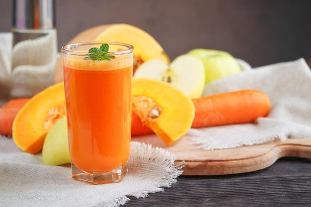 Succo di frutta fresco, mix di frutta e verdura su un tavolo di legno