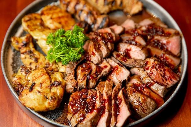 Assortimento succoso fresco di carne alla griglia affettata che si trova su un piatto grande e rotondo