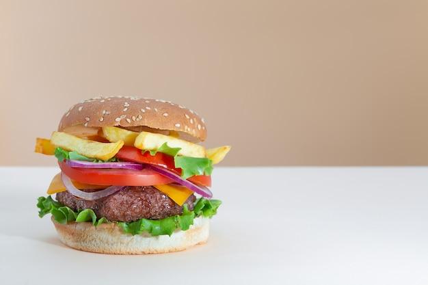 Hamburger di manzo succoso fresco con patatine fritte posto su sfondo alla moda creativo beige e marrone