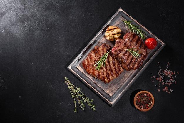 Bistecca di manzo deliziosa succosa fresca su uno sfondo scuro. piatto di carne con spezie ed erbe aromatiche