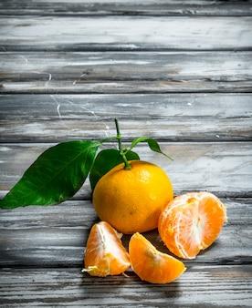 Mandarini freschi e succosi con foglie. su legno