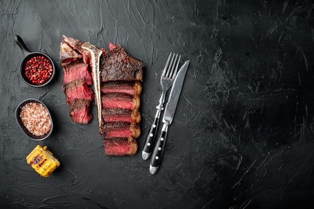 Fresco e succoso medio raro a fette e arrosto di osso a t o porterhouse bistecca di carne di manzo set, sulla pietra nera tavolo, vista dall'alto piatto