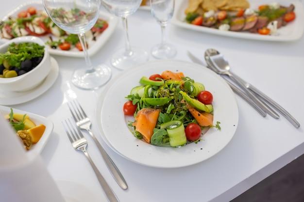 Insalata di valeriana fresca con avocado, cetriolo, salmone, pomodorini. condimento con miele, senape di digione, olio d'oliva e succo di limone, guarnito con semi di chia. preparato dallo chef.