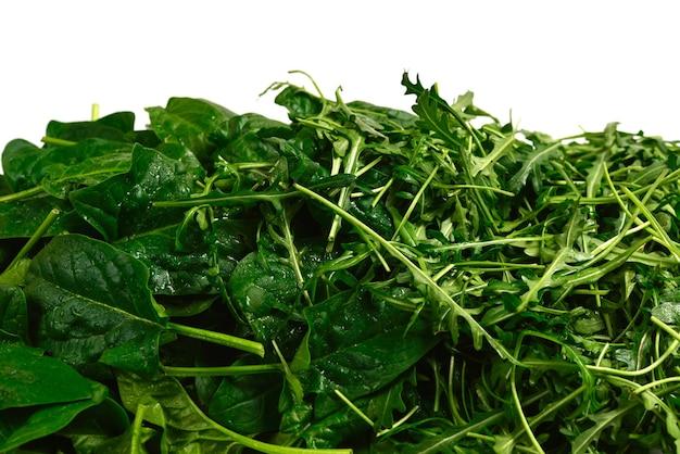 Foglie fresche di rucola e spinaci come sfondo.