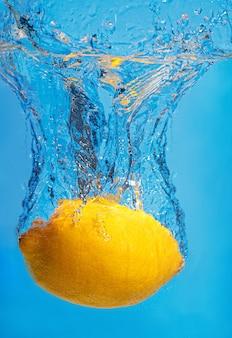 Il limone fresco scende in acqua con una spruzzata su uno spazio blu