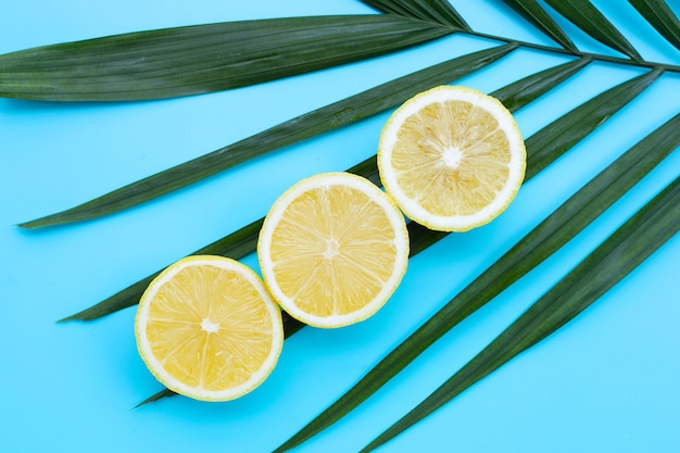 Limone fresco su foglie verdi su superficie blu