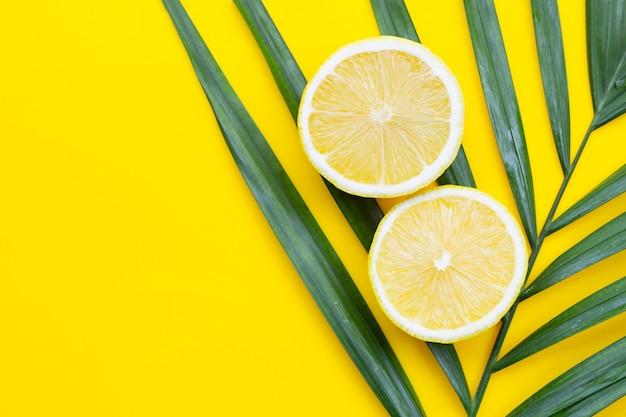 Limone fresco su foglie di plam tropicali su sfondo giallo.