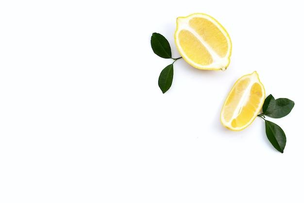 Limone fresco con foglie verdi su sfondo bianco.