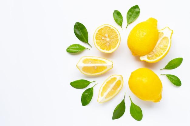 Limone fresco con le foglie isolate su bianco