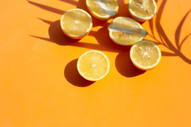 Limone fresco con foglia di palma sulla superficie arancione