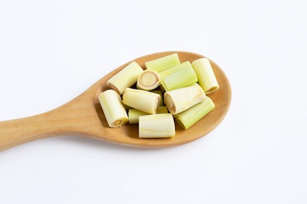 La citronella fresca ha tagliato i pezzi sul cucchiaio di legno su bianco