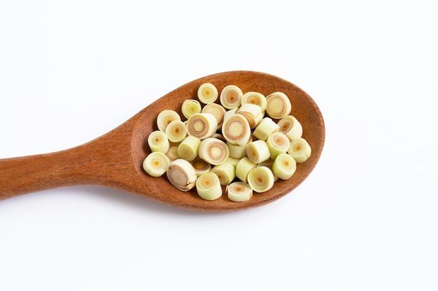 Fette fresche della citronella sul cucchiaio di legno su bianco