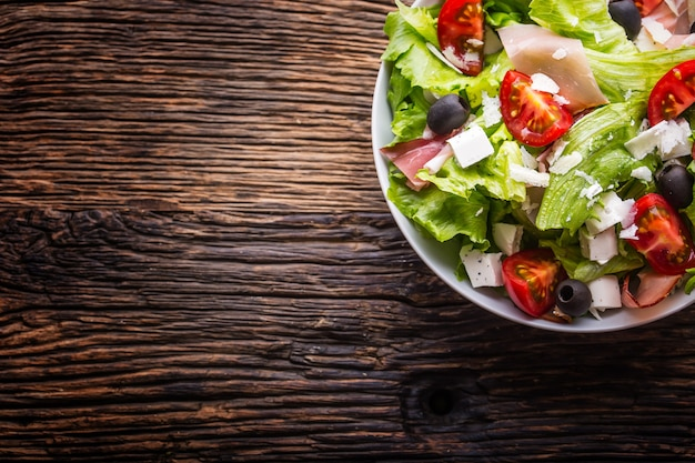 Insalata di lattuga frescainsalata mediterranea sana olive pomodori parmigiano e prosciutto