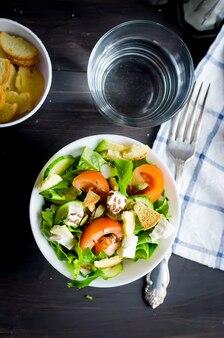 Insalata verde chiara fresca con verdure e formaggio e un bicchiere d'acqua per pranzo su un tavolo scuro